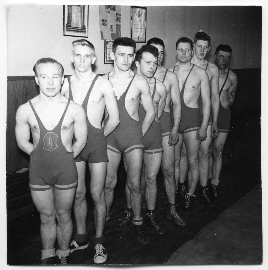 Åtta män i trikåer uppställda på rad.