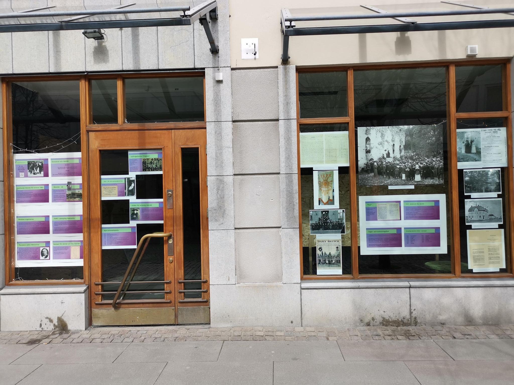 Fotografi av utställning monterad på butiksfönster ut mot gågata.